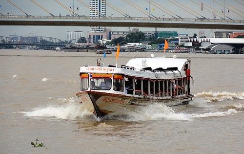 An Orange Line Chao Phraya Express Boat approaching Phra Arthit Pier in Banglamphu District of Bangkok
