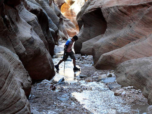 Walking inside the slot in Willis Creek Canyon in Grand Staircase Escalante National Monument in Utah